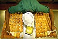 US Navy 031114-N-9769P-054 Mess Management Specialist Seaman Lamar Hardy, from Indianapolis, Ind., applies butter to freshly baked dinner rolls.jpg