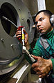 US Navy 040426-N-8148A-027 Aviation Boatswain's Mate Equipment Airman Jorge Linarez, of North Plainfield, N.J., applies grease to a purchase cable in a machinery room.jpg