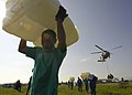 US Navy 050131-N-6074Y-110 Indonesian citizens carry plastic containers away from U.S. helicopter drop zone.jpg