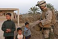 US Navy 060315-M-0374B-004 A U.S. Navy Corpsman assigned to Fox Company, 2nd Battalion, 6th Marines, Regimental Combat Team Five, gives a couple of sweets to Iraqi children during a patrol through fields along the Euphrates Riv.jpg