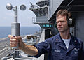 US Navy 060508-N-0933M-001 Aerographer's Mate 3rd Class Arthur Bourke measures wind speed and direction with a handheld anemometer on the island aboard the Nimitz-class aircraft carrier USS Dwight D. Eisenhower (CVN 69).jpg