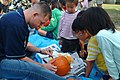 US Navy 061028-N-4124C-029 Gunner's Mate 3rd Class Eric Young, assigned to amphibious transport dock USS Juneau (LPD 10), instructs kids of a local children's home on how to carve a pumpkin as part of a community.jpg