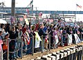 US Navy 061120-N-8655E-028 Family members of the sailors aboard Los Angeles-class fast-attack submarine USS Albany (SSN 753) cheer and wave flags as the sub returns home from a six-month deployment.jpg