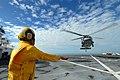 US Navy 070617-N-8704K-045 Aviation Boatswain's Mate (Handling) 3rd Class Luis Dominguez signals an MH-60S Seahawk aboard Military Sealift Command hospital ship USNS Comfort (T-AH 20).jpg