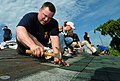 US Navy 070706-N-3832S-057 Cyptologic Technician Technical 1st Class Jason Guidry nails shingles onto the roof of a house during a community relations project with Habitat for Humanity.jpg