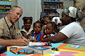 US Navy 070921-N-7088A-125 Cmdr. Craig Martin, attached to Military Sealift Command hospital ship USNS Comfort (T-AH 20), examines a family at the at Moulton Hall Methodist Primary School.jpg