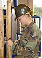 US Navy 080114-N-0000X-004 Construction Electrician 3rd Class Jennifer Janzen, assigned to Naval Mobile Construction Battalion (NMCB) 5, uses an electrical training model to give a lecture on quality construction.jpg