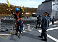 US Navy 100409-N-1559J-055 Seaman Miguel Mora throws a heaving line to USS Vella Gulf (CG 72) during sea and anchor detail aboard USS Laboon (DDG 58).jpg