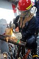 US Navy 101011-N-7293M-378 Damage Controlman Fireman Kyle Lobb hammers a wooden wedge and oakum material into a gash in a training pipe.jpg
