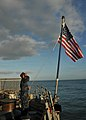 US Navy 110509-N-NL541-028 Seaman Jeremy Inmaniannuzzo raises the national ensign during morning colors aboard USS Thach (FFG 43).jpg
