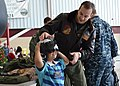 US Navy 111203-N-VA590-098 Lt. Cmdr. Jeremy Fischer, assigned to Logistics Support Squadron (VR) 57, helps a child put on a flight helmet during th.jpg