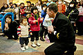 US Navy 120207-N-CZ945-102 Lt. j.g. Geordie Kelly, fleet band master of U.S. 7th Fleet Band, shows children how to use a maraca shaker during a per.jpg