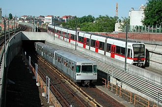 Vienna U-Bahn - Vienna U-Bahn trains of both types leaving Längenfeldgasse station: left, standard train on line U4 with third rail power; right, T-cars train on U6 powered by overhead lines