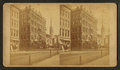 View of a commercial street, including a church, by Milan P. Warner.png