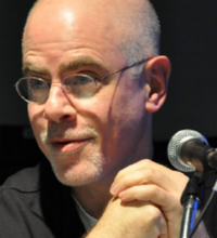 A photograph of a bald man wearing glasses and a black shirt. He is looking toward his right while a microphone is shown to the image's right.