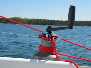 Winch - Modern self-tailing winch on a sailing boat. Here, the line winched is a jib or spinnaker sheet which runs from the sail (upper left, not shown) to a block (lower right,not shown) and from there to the lower part of the winch. The handle is detachable to facilitate handling of the line.