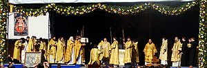 Entrance (liturgical) - Great Entrance at an outdoor hierarchical Divine Liturgy. In the center the protodeacon with the diskos is kneeling in front of the bishop.