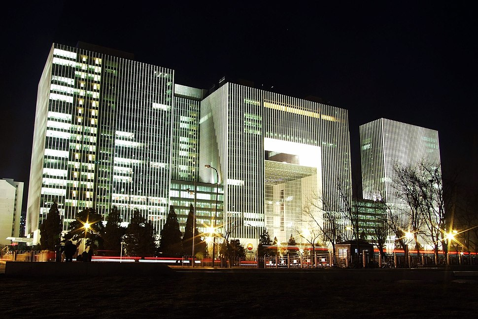A tall modern office building of three flat-roofed rectilinear blocks joined by smaller hyphens. It is seen at night, with some of its windows lit.