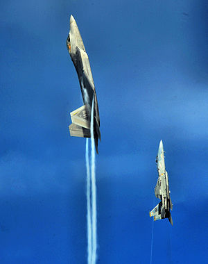 57th Wing - An F-22A Raptor and F-15C Eagle from the U.S. Air Force Weapons School's 433rd Weapons Squadron pull into a vertical climb over the Nevada Test and Training Range July 16, 2010.
