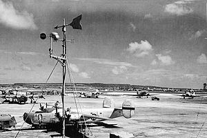 "East Field (Saipan) - Ramp at East Field, fall 1944.  Consolidated B-24J-105-CO Liberator 42-109809 ""Evasive Action"" 819th Bomb Squadron from the 30th Bomb Group, C-47 Skytrains and, in the distance, a B-29 Superfortress"