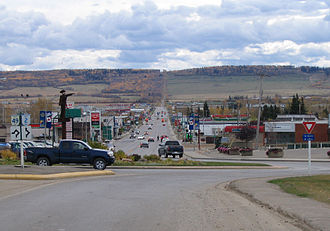 Dawson Creek - Looking south past traffic circle down 8 Street, with the metal statue pointing the way northwest to Alaska.
