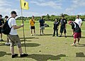 A Special Olympics athlete, right, putts as U.S. military volunteers look on during the 2nd annual Special Olympics of Guam golf exhibition Dec 111217-N-AZ907-007.jpg