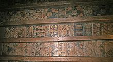 Four wooden beams with three sets of coloured paintings between them, made up of fruit, flowers and other patterns.