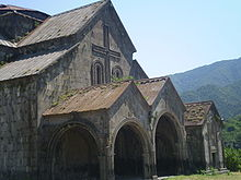 Gabled roof with extensions over a covered entrance with two gabled arches.