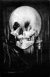 Vu de près, l'image représente une femme à sa toilette qui se regarde dans un grand miroir; avec un peu de recul, le miroir rond semble représenter un grand crâne, dont les orbites sont la coiffure sombre de la dame et son reflet.