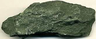 Homestake Mine (South Dakota) - Typical auriferous greenschist gold ore from the Homestake Mine. Two small masses of native gold (Au) are visible near the bottom right.