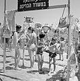 Badgasten bij hekwerk waar tassen, hoeden en handdoeken over heen hangen, Bestanddeelnr 255-1964.jpg