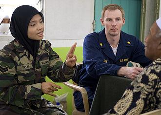 Rejimen Askar Wataniah - RAW Corporal Intan Badri, observed by US Navy Lieutenant Commander Scott Bannan, screening a patient during a CARAT Malaysia 2009 medical civil action project at Seberan Tayor Primary School in Kuantan, Malaysia, on 24 June 2009.
