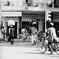 COLLECTIE TROPENMUSEUM Straatbeeld in Ouagadougou met op de achtergrond een apotheek mannen op brommers en met lasten op het hoofd TMnr 20010432.jpg