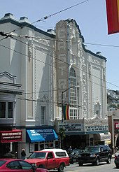 "Color photograph of the exterior of a movie theater, showing 1990s-2000s-era automobiles on the street in front of the theater, electric lines above the cars, and shop windows and awnings along the sidewalk. The theater features a large vertical 'blade' that reads ""Castro"", a marquee announcing film showings, and a facade which includes a mission-revival arch and highly ornamented panels designed in the Churrigueresque style."