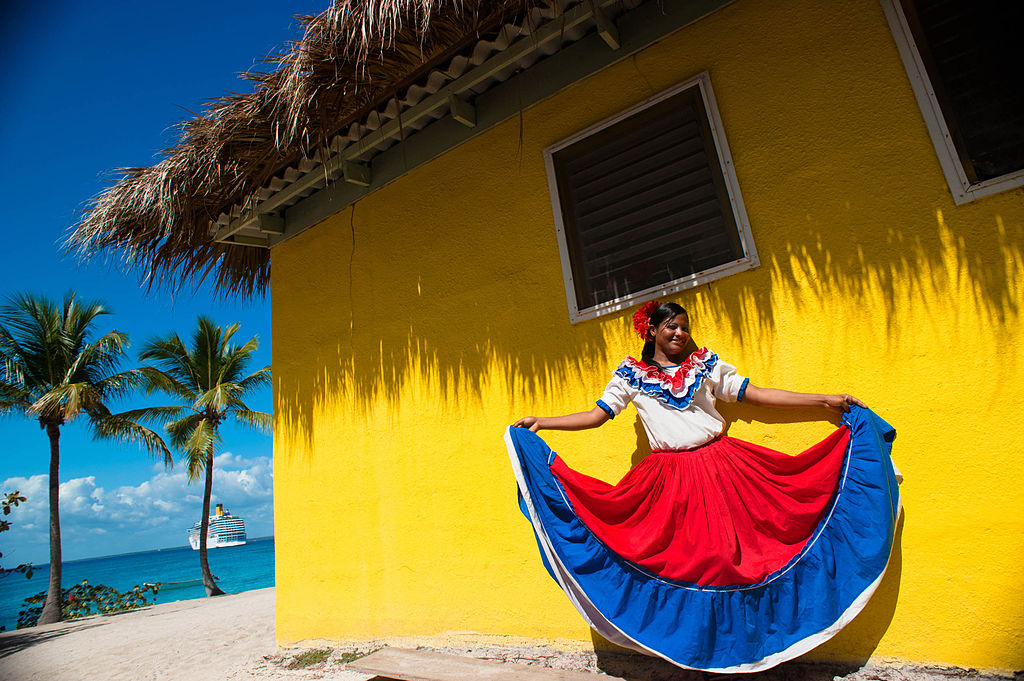 Catalina Island, Dominican Republic. A woman in traditional outfit in front of a bungalow on a seashore (full length portrait)