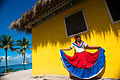 Catalina Island, Dominican Republic. A woman in traditional outfit in front of a bungalow on a seashore (full length portrait).jpg