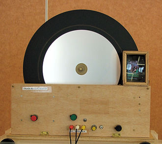 Mechanical television - A colour televisor. A test card (the famous test card F) can just be seen through the lens on the right.