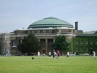 In the foreground is a grass field with seven male students playing soccer. A two-storey building is beyond the field, topped by an arched and nearly-triangular green-copper dome. A light grey-blue sky is visible in the top third of the image, with a helicopter in the distance on the right. Four automobiles are parked in front of the building along its length, and horizontally to it.