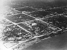 Aerial black and white image of a destroyed city along the coast. Almost all buildings are flattened.