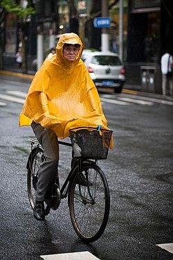 Cyclist wearing a yellow rain poncho in Shanghai, China -- June 2011.jpg