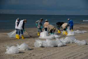 Environmental impact of the Deepwater Horizon oil spill - Workers cleaning up a beach during Deepwater Horizon oil spill