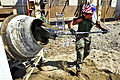 Defense.gov News Photo 120222-A-TF780-025 - U.S. Marine Corps Staff Sgt. Mario Vargas shovels cement into a mixer to make concrete at the National School of Caracol in Caracol Haiti on Feb.jpg