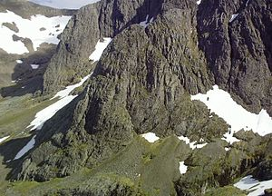 Harold Raeburn - The west face of the Douglas Boulder below Ben Nevis, Highland Scotland. The left edge approximates to the line of Direct Route (215m Very Difficult) first climbed on 3 April 1896 by a party of four led by William Brown and including Raeburn – his first climb on Ben Nevis. The steep crest behind (left) is Raeburn's Arete (230m Severe), climbed on 30 June 1902 in the company of William and Jane Inglis Clark. The (almost) level Carn Mor Dearg Arete is on the skyline.