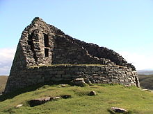 The ruins of a stone building set on a grassy knoll with blue skies above. The building is circular  in outline and all that remains of the structure are the double-skinned walls that rise to two stories in places.