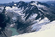 A view looking down on a range of dark mountains. The valley to the left contains a light-colored glacier. There is a small lake at the bottom of the picture.