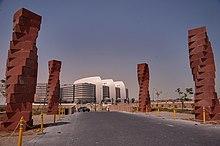 Vier kronkelende rode kolommen staan langs een weg die leidt naar een modern bruin en wit gebouw.