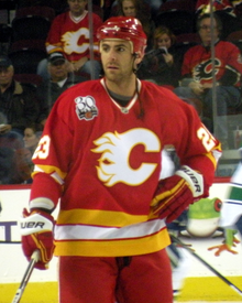 "A hockey player stands and looks to his right during a pre-game warm up. He is wearing a red uniform with white and yellow bands at the waist and elbows, and a stylized ""C"" logo on his chest."