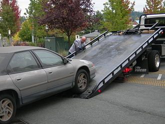 Accident Towing Services Act - A car being loaded onto a flatbed tow truck.
