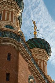 Vue en contre-plongée de la croix au sommet d'une tour d'une cathédrale orthodoxe russe à mur rouge et toiture bleue.