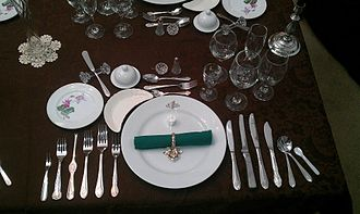 Salt cellar - Formal place setting for a 12 course dinner; individual salt cellar at top of place setting.